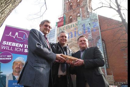 Dr. Bernd Schwarze (links im Bild) hält gemeinsam mit Theo Dräger (mitte) und Fundraiser Christian Hohmann (rechts) einen Rippenstein. Im Hintergrund ist links das Logo von den Sieben-Türmen auf einem Roll-up zu sehen. Auf der rechten Seite im Hintergrund ist St. Petri zu sehen. - Copyright: Ev.-Luth. Kirchenkreis Lübeck-Lauenburg