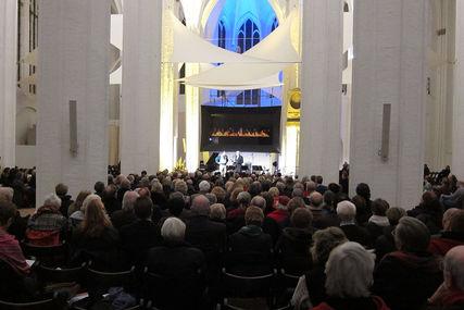 Im Vordergrund sind viele sitzende Personen auf Stühlen von hinten zu sehen. Sie schauen auf eine beleuchtete Bühne. Auf der Leinwand ist ein brennendes Kaminfeuer zu sehen. Auf der Bühne stehen zwei Personen. Hinter ihnen steht ein Klavie und Notenständer, sowie Mikrofone. Die Fenster von St. Petri hinter der Leinwand sind blau beleuchtet. - Copyright: Ev.-Luth. Kirchenkreis Lübeck-Lauenburg