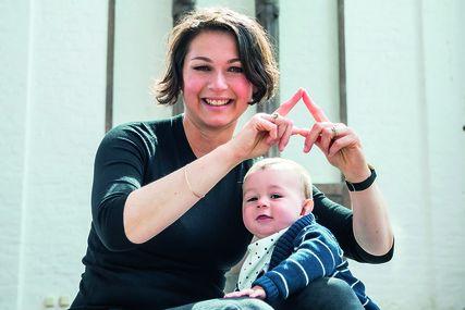 Patricia Wickowski-Simmgen mit Kind zeigt das Sieben-Türme-Symbol mit ihren Fingern. Sie ist in der Hocke und ihr Kind stützt sich auf ihr linkes Bein auf.  - Copyright: Olaf Malzahn